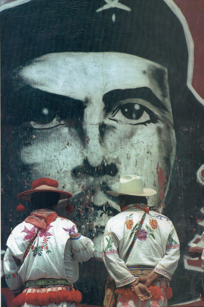 Indígenas chiapanecos frente a un mural.
